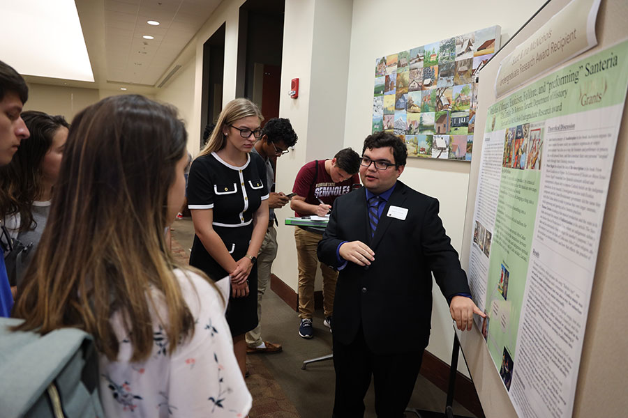 "Senior Elias Larralde explains his project, ""Melodies of Mirages: Exoticism, Folklore, and'performing' Santeria."" (Bayard Stern)"
