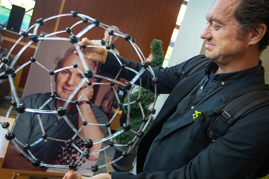British physicist Jonathan Hare demonstrates a model of a buckyball in front of a photo of the late Sir. Harold Kroto.