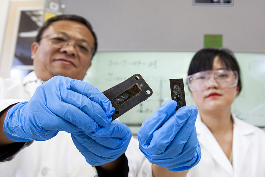 Professor Zhiyong (Richard) Liang and research faculty member Ayou Hao holding pieces of carbon fiber reinforced polymer composites coated with a protective heat shield made of a carbon nanotube sheet that was heated to a temperature of 1,900 degrees Celsius.
