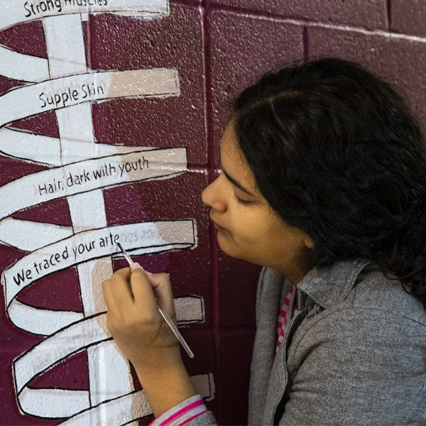 Melissa Gonzalez-Lopez works on her mural in the anatomy lab. It includes a poem that thanks the families of people who donated their bodies for medical instruction. Photo by Colin Hackley / FSU College of Medicine