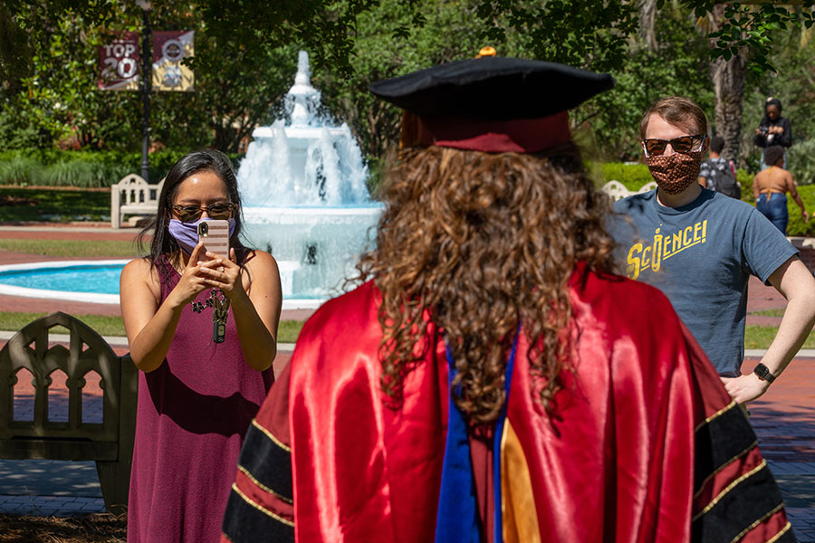 An FSU spring graduate takes photos on Westcott Plaza on May 1, 2020. (FSU Photography Services)