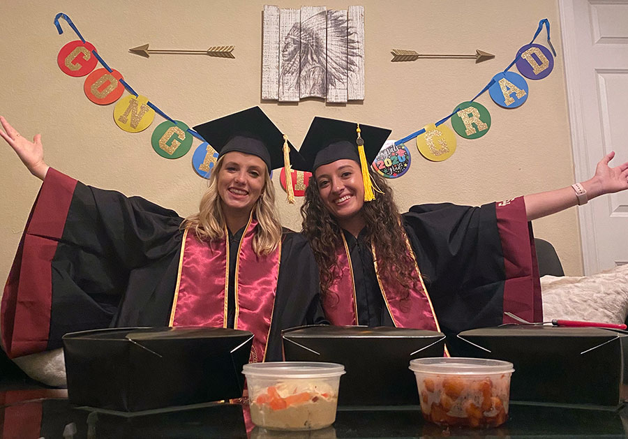 Ashley Sanders and her roommate, Melissa Beale, wear their caps and gowns as they watch virtual commencement and enjoy curbside pick-up from Madison Social. (Ashley Sanders)