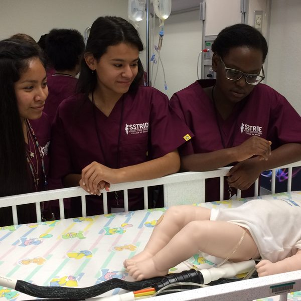 From left, SSTRIDE students Britney Garcia, Gisselle Nava and Ruth Bellevue observe how to take a brachial pulse in a baby. Courtesy of FSU College of Medicine