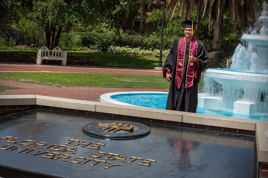 A graduate poses at Westcott Fountain before FSU's virtual summer commencement ceremony July 31, 2020.