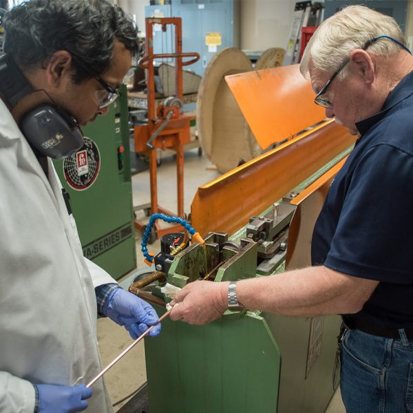 Research scientists Shreyas Balachandran, left, and William Starch draw lengths of niobium-tin superconducting wire at the Applied Superconductivity Center at the National High Magnetic Field Laboratory. A new grant of $1.5 million will allow the group to continue this research. Photo: Stephen Bilenky