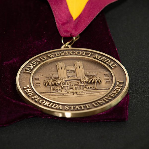 """TheJames D. Westcott Distinguished Service Medalrecognizesa """"person whose distinguished service merits exceptional recognition and whose life and work exemplifies the Vires, Artes and Mores, which the university seeks to nurture in its students."""""""