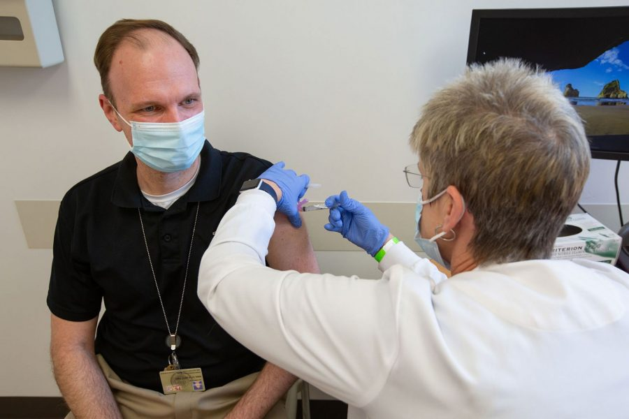 Dr. Christopher DeLisle receives the COVID-19 vaccine from Corey Williams, RN supervisor at University Health Services. (FSU Photography Services)