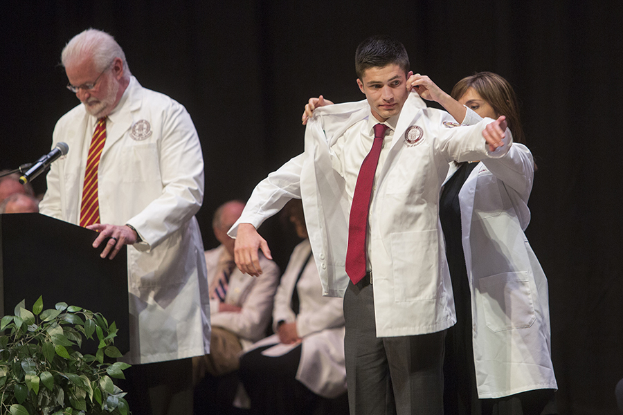 Jimmy Brown receives a white physician's coat during a 2017 ceremony at the FSU College of Medicine. Brown, a member of the M.D. Class of 2021, became the first student to recieve the Nancy Van Vessem, M.D. Memorial Scholarship. (FSU Photography Services)