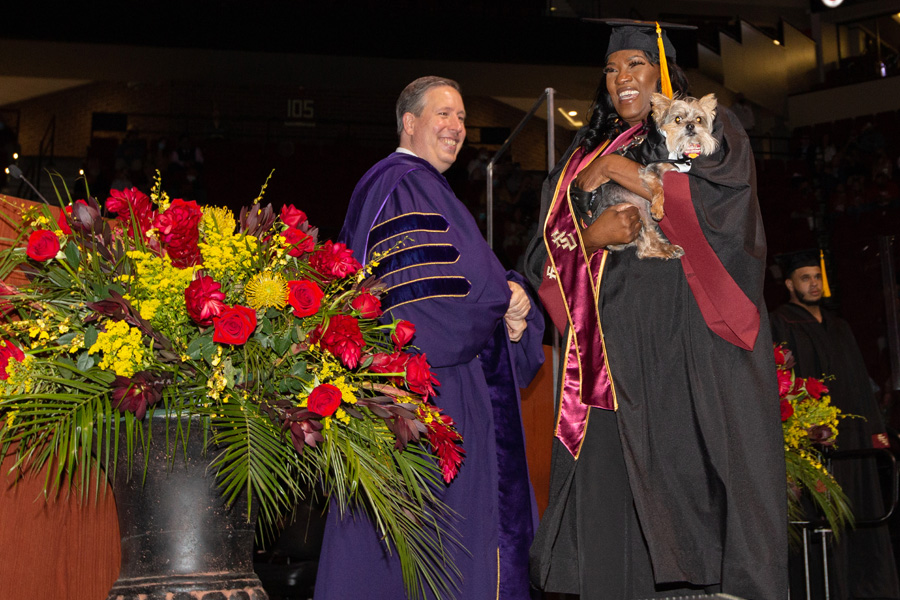 College of Social Sciences and Public Policy Dean Tim Chapin congratulates a graduate and her puppy during FSU Spring Commencement Friday, April 23, 2021. (FSU Photography Services)