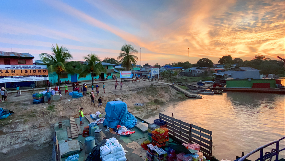 """Marcos Colón, """"Sunset in San Isidro,"""" villagers unload cargo from the ship in San Isidro, Peru, March 2020."""