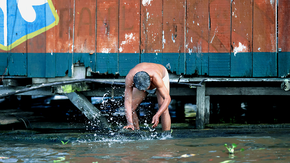 """Marcos Colón, """"Cooling Down in the Sun,"""" a man takes a bath outside his home in Belén, Iquitos, Peru, March 2020."""