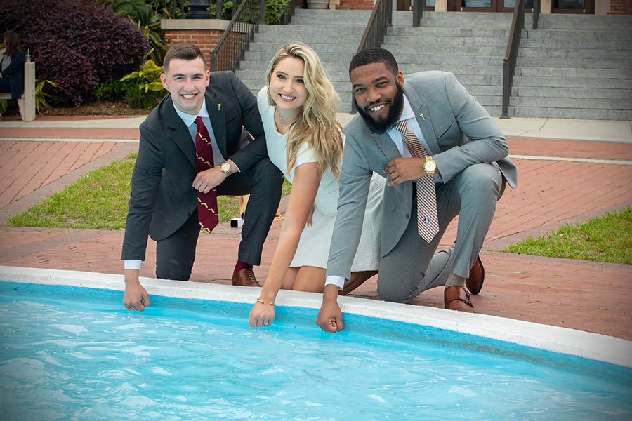 FSU graduates dip their class rings into Westcott Fountain during ring pick-up Thursday, April 8, 2021. (FSU Photography Services)
