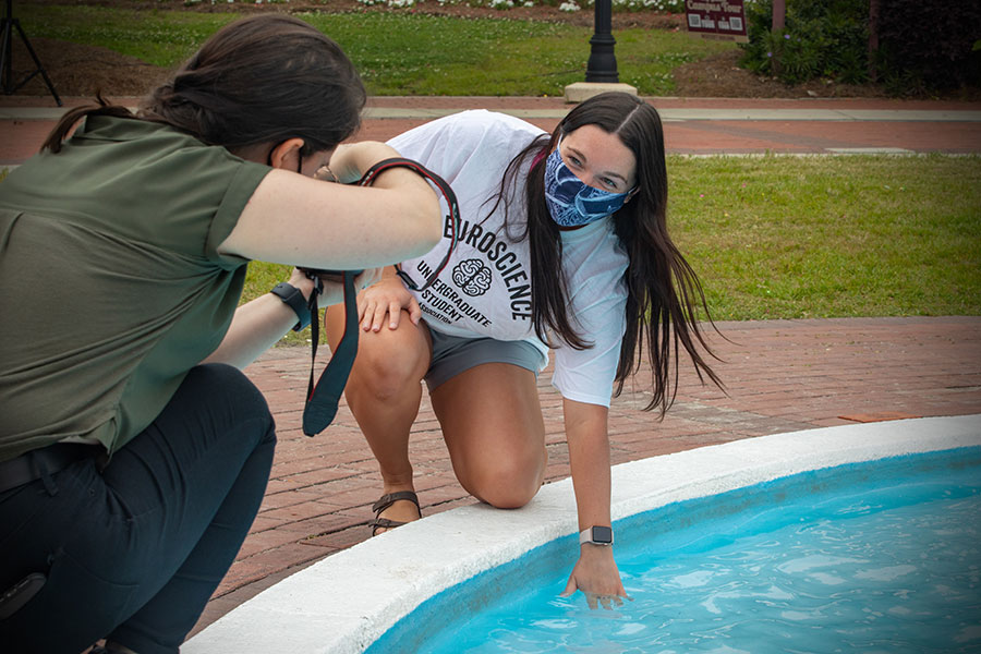 An FSU graduate dips her class ring into Westcott Fountain during ring pick-up Thursday, April 8, 2021. (FSU Photography Services)