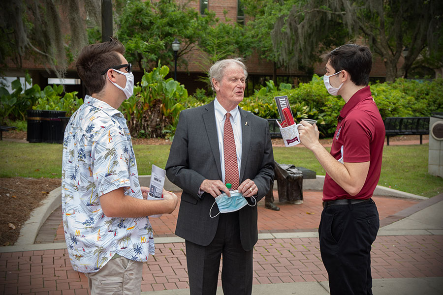 FSU graduates chat with President John Thrasher during ring pick-up at Westcott Fountain Thursday, April 8, 2021. (FSU Photography Services)