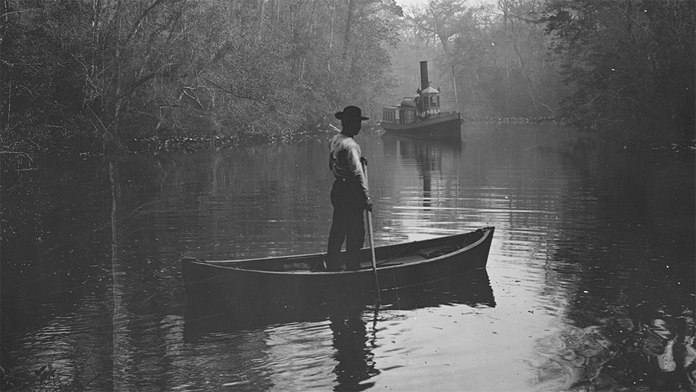 Archival photograph (c. 1880-1897) of a man standing in a canoe, steamboat in background; in Deep Creek, Florida. (Photo courtesy of Library of Congress)