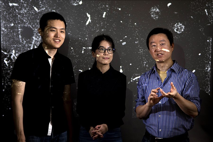 From left, postdoctoral researcher Yuan Tang, FSU graduate student Toshiaki Kanai, and FAMU-FSU College of Engineering professor Wei Guo discuss the movement of tracking particles in liquid helium of their particle tracking velocimetry system at the National High Magnetic Field Laboratory. (Mark Wallheiser/FAMU-FSU College of Engineering)