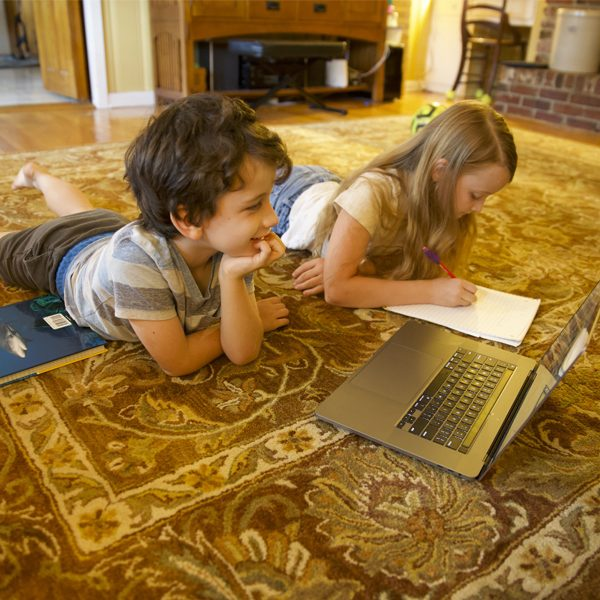 A first-grade student and fourth-grade student learning from home through the digital academy at Gilchrist Elementary School. (Courtesy of Robert Schoen)