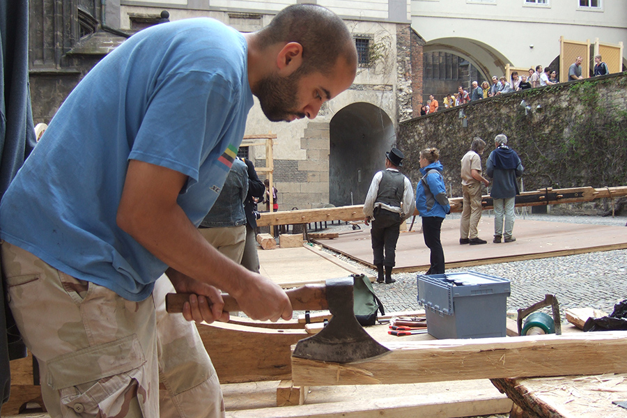 Duarte hewing a timber during the construction of human-powered wooden crane at Prague Castle in the Czech Republic