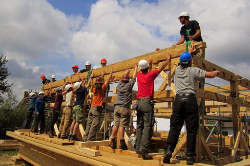 Students and professional timber-framers working together during the Gwozdziec synagogue reconstruction in Sanok, Poland