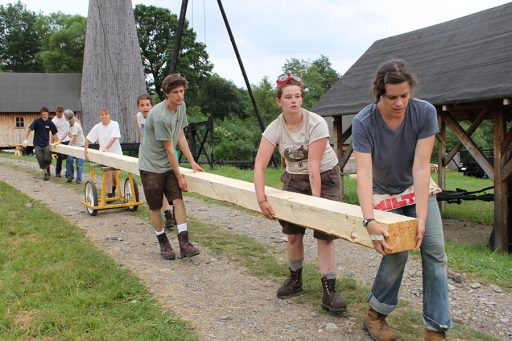Students transporting a hewn timber during the reconstruction of the Gwozdziec synagogue in Sanok, Poland