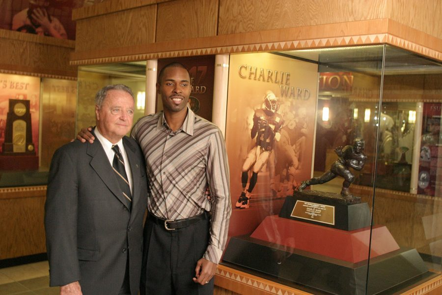 Coach Bowden poses with Charlie Ward in 2006 in front of Ward's 1993 Heisman Trophy, which is displayed in the Moore Athletic Center. (FSU Photography Services)