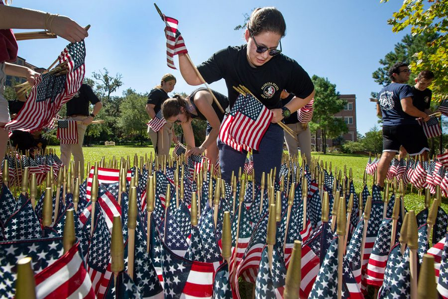 Army ROTC Cadet Marie D'Addario helps plant flags as part of a commemoration of the 20th anniversary of the Sept. 11 attacks.