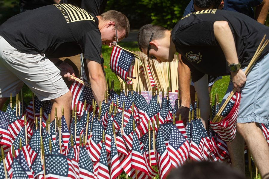 Joshua Peach and Eric Wimmer help plant flags as part of a display to commemorate the anniversary of the Sept. 11 attacks and honor the lives that were lost.