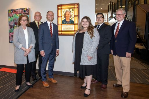 From left: Anne Rowe, Bruce Janasiewicz, Joe O'Shea, Cara Axelrod, Brendan Gonzalez and Jim Lee gather around the stained-glass window was unveiled in honor of the late Karen Laughlin during a celebration of her legacy Oct. 21, 2021, at Florida State University's Honors, Scholars and Fellows house. (FSU Photography Services)